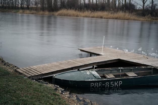Pier am fluss mit kleinem boot