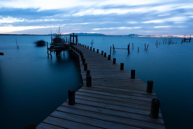 Pier auf dem meer umgeben von hügeln unter einem bewölkten himmel am abend in portugal