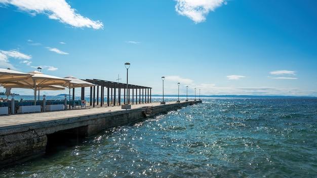 Pier mit café, regenschirmen, pavillon und laternenpfählen, ägäisches meer in nikiti, griechenland