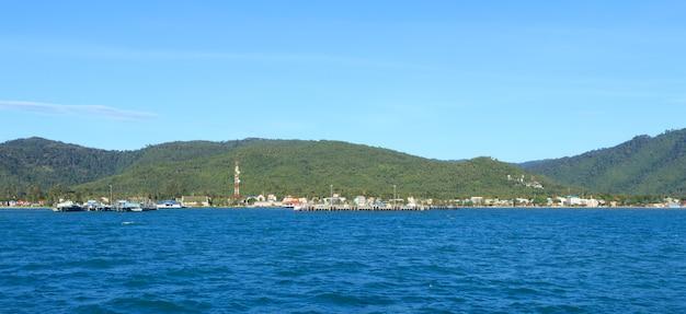 Pier seestück mit geschwollenen weißen wolken und grünem berg, thailand