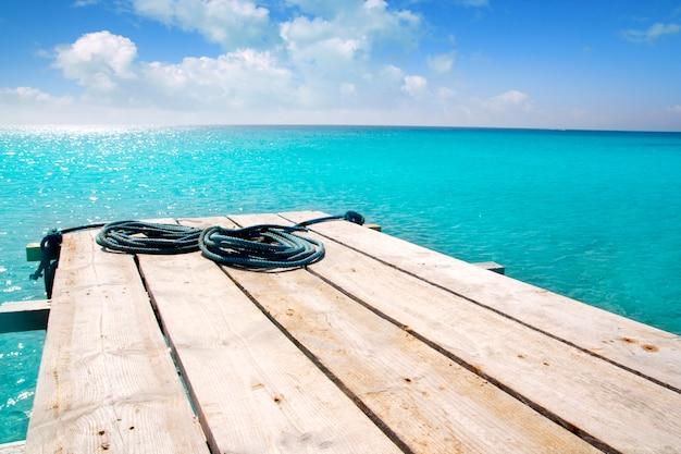 Pier-türkis-balearenmeer des formentera-strandes hölzerner