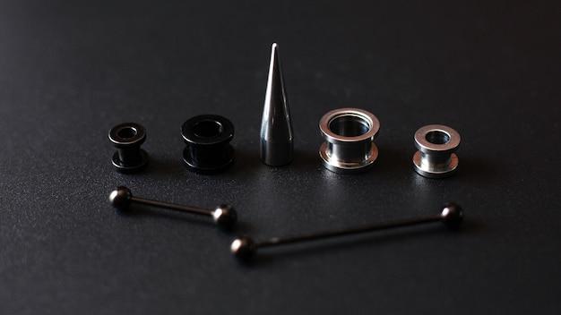 Piercing-accessoires auf einem schwarzen edelstahlschmuck für pannenliebhaber.