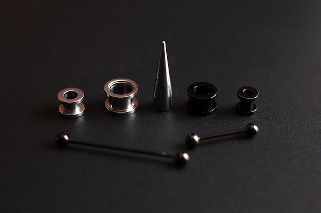 Piercingzubehör auf schwarzem rostfreiem metallschmuck der nahaufnahme für durchstichliebhaber