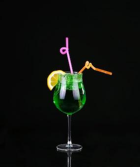 Piggelin drink, bestehend aus wodka, melonenlikör und zitronen-limetten-soda auf schwarz