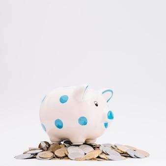 Piggybank über den münzen gegen weißen hintergrund