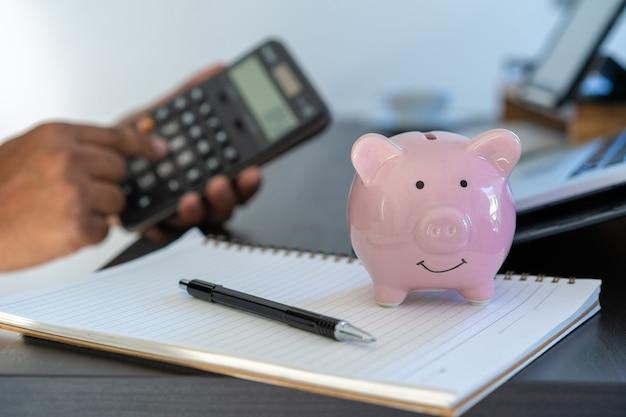 Piggybank und taschenrechner auf dem schreibtischgeschäftsdokumentenrechner, der geld zählt