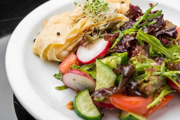 Pikante buchweizenpfannkuchen mit kirschtomaten, rucolasalat, spinat, parmaschinken,