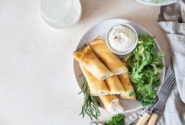 Pikante crepes oder dünne pfannkuchen mit hühnchen, serviert mit grünem salat und bechamelsauce