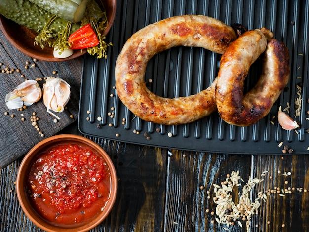 Pikante hausgemachte würstchen mit schweinefleisch und rindfleisch, gegrillt mit sauce, gewürzen und eingelegter gurke