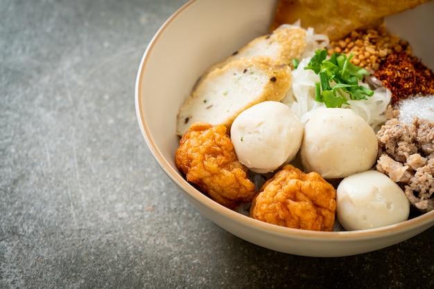 Pikante kleine reisbandnudeln mit fischbällchen und garnelenbällchen ohne suppe - asiatische küche