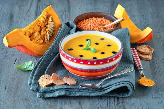 Pikante kürbissuppe mit roten linsen und kurkuma serviert mit minzblättern und tropfen balsamico-essig
