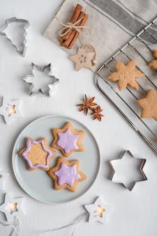 Pikante lebkuchenplätzchen mit violettem zuckerguss auf grauer platte auf weißem holztisch mit schneidern