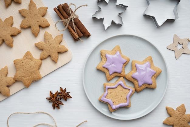 Pikante lebkuchenplätzchen mit violettem zuckerguss serviert auf grauem teller auf holztisch mit schneidern