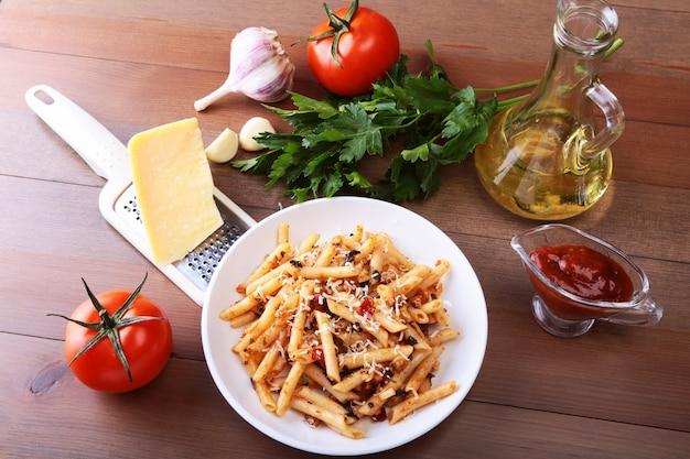 Pikante pasta penne bolognese mit gemüse, chili und käse in tomatensauce.