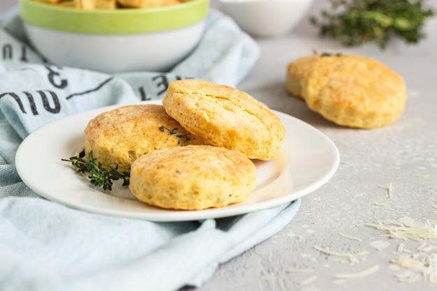 Pikante scones oder kekse mit käse und thymian auf einer weißen keramikplatte.
