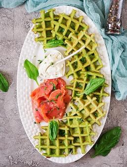 Pikante waffeln mit spinat und frischkäse, lachs in weißer platte. leckeres essen. draufsicht. flach liegen