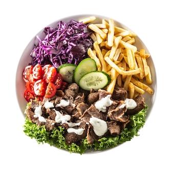 Pikanter türkischer kalbskebab mit draufsicht, serviert mit frischem gemüse, salat, französischem feuer und köstlichem dip, mayonnaise.