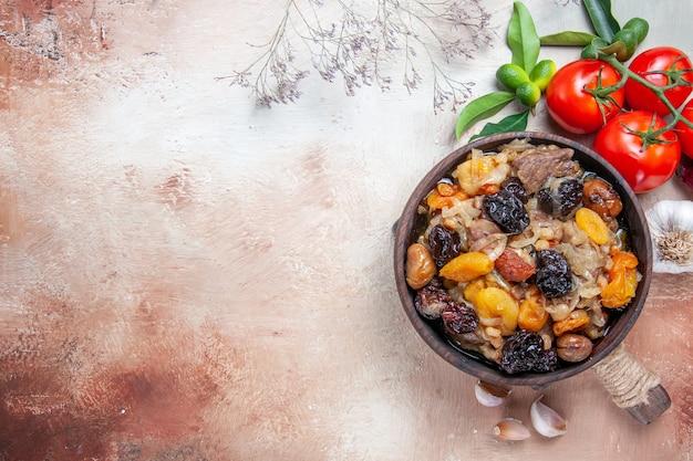 Pilafschale des pilafs von oben nahansicht pilaw auf dem schneidebrett tomaten zitrusfrüchte knoblauch