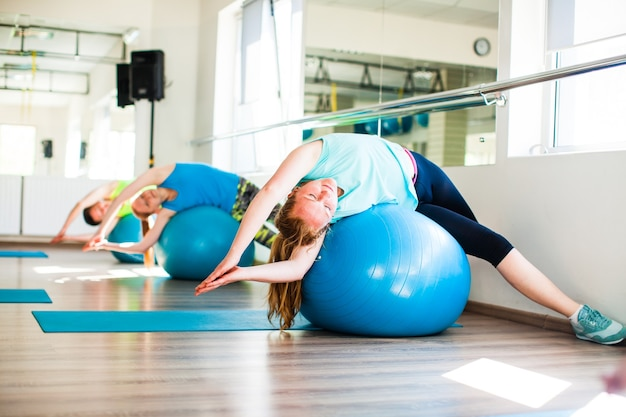 Pilates-dehnungstraining. frauen auf einem fitnessball im fitnessstudio