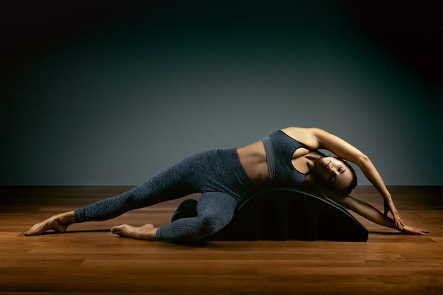 Pilates, eignung, sport, training und leutekonzept - frau, die übungen auf einem kleinen fass tut. fitness-konzept