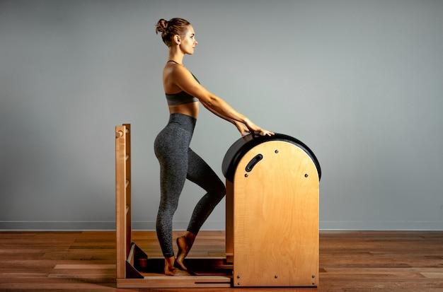 Pilates, fitness, sport, training und personenkonzept - frau, die übungen auf einem kleinen fass macht. korrektur des antriebsapparats, korrekte haltung.