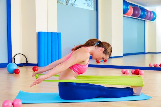 Pilates-frau, die gummibandübung rudert