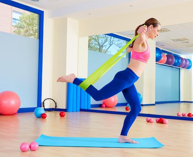 Pilates-frau, die gummibandübung steht