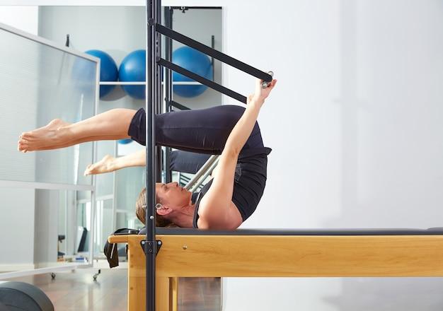 Pilates-frau im reformer rollen vorbei übung