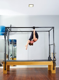 Pilates frau in cadillac akrobatik umgedreht