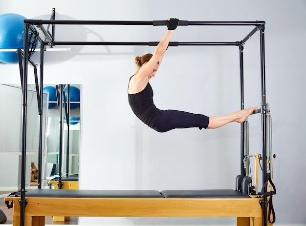 Pilates-frau in cadillac akrobatischem reformer