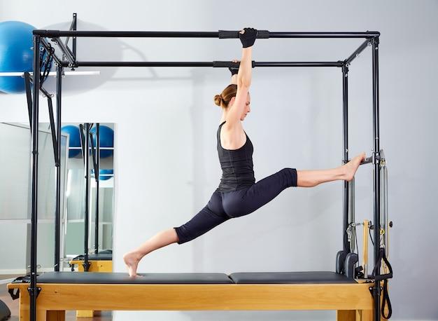 Pilates-frau in cadillac-beinen spaltete reformer auf