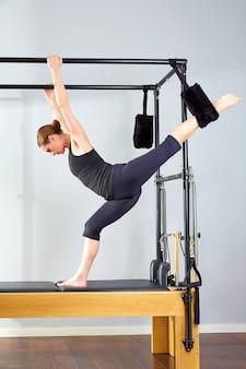 Pilates-frau in cadillac-gespaltenen beinen dehnen übung aus