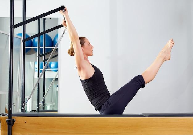 Pilates-frau in der reformer-teaserübung an der turnhalle