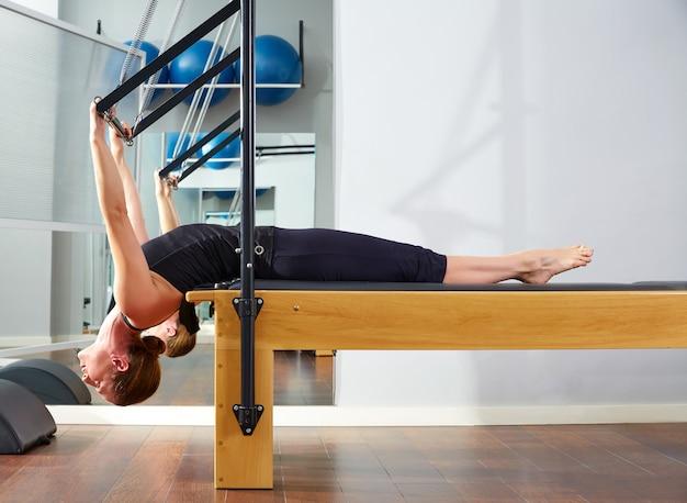 Pilates-frau in der reformerübung an der turnhalle
