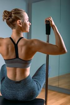 Pilates-frau in einem cadillac-reformer, der dehnungsübungen im fitnessstudio macht