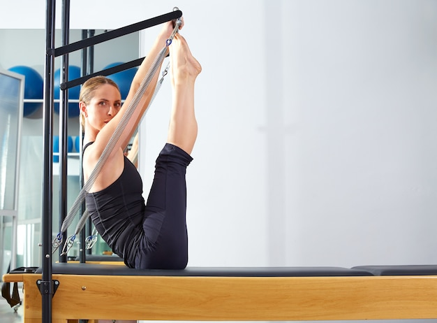 Pilates-frau in reformer-monki-übung