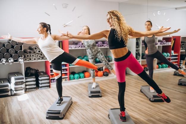 Pilates-gruppe, die in einer turnhalle ausarbeitet