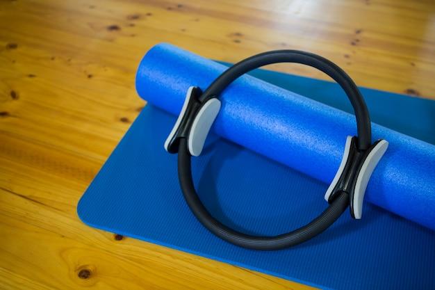 Pilates ring und trainingsmatte auf holzboden gehalten
