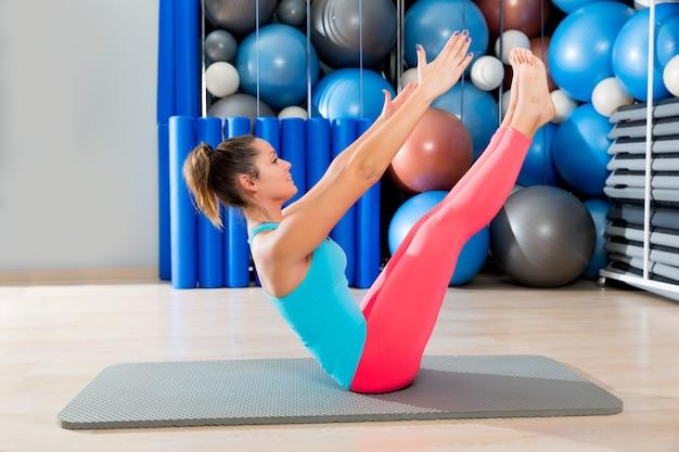 Pilates-teaser-übungsfrau auf der mattengymnastik innen