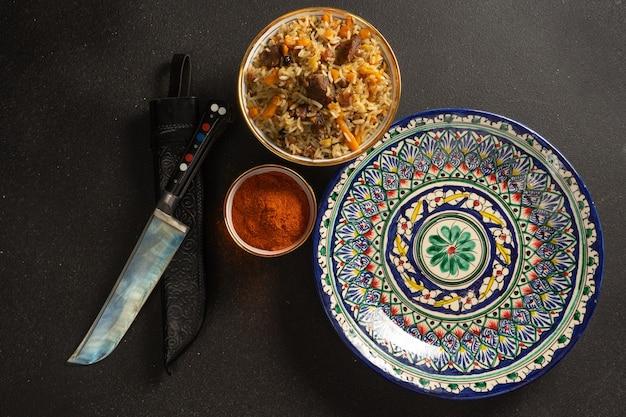 Pilaw ist ein traditionelles reisgericht mit lamm oder rind und gemüse in ethnischen usbekischen keramikgerichten.