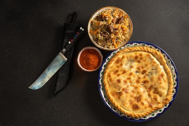 Pilaw ist ein traditionelles reisgericht mit lamm oder rind und gemüse und heißem kuchen in ethnischen usbekischen keramikgerichten.