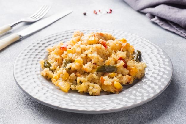 Pilaw mit gemüse und huhn in einer grauen platte auf einem grau.