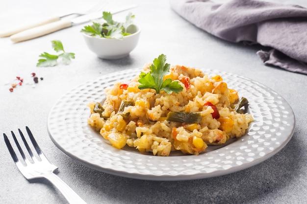 Pilaw mit gemüse und huhn in einer grauen platte auf einem licht.