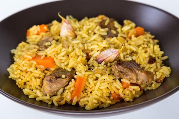 Pilaw mit lamm, karotten, zwiebeln, knoblauch, pfeffer und berberitze. ein traditionelles gericht der asiatischen küche.