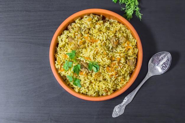 Pilaw mit rindfleisch, karotten, zwiebeln, knoblauch, pfeffer und kreuzkümmel. ein traditionelles gericht der asiatischen küche.