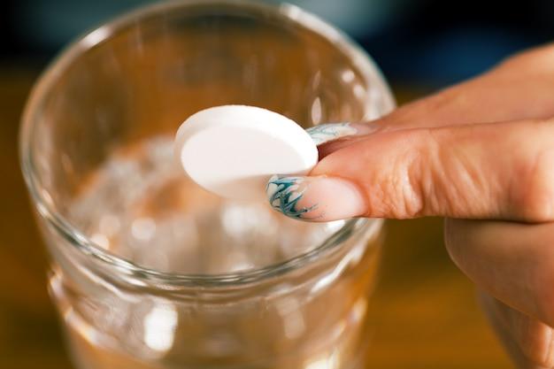 Pille wird über ein glas wasser gehalten