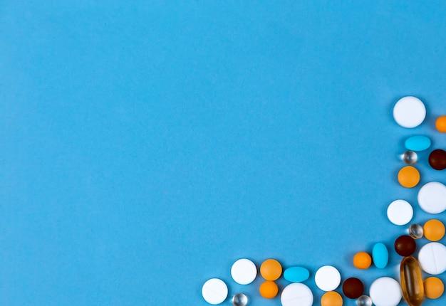 Pillen als grenze gesetzt. farbige pillen stellten als rand auf blauem hintergrund ein