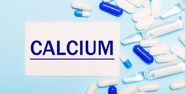 Pillen, ampullen und eine weiße karte mit dem text calcium auf hellblauem hintergrund. medizinisches konzept