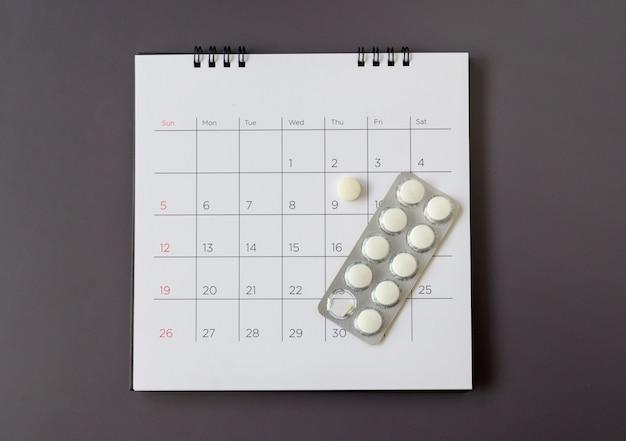 Pillen auf einem kalenderhintergrund. konzept gesundheitswesen