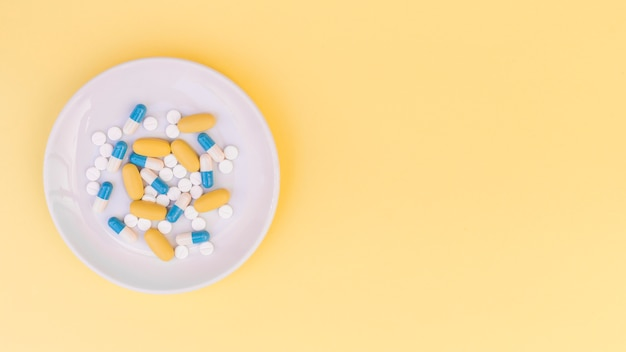 Pillen auf weißer platte über dem gelben hintergrund